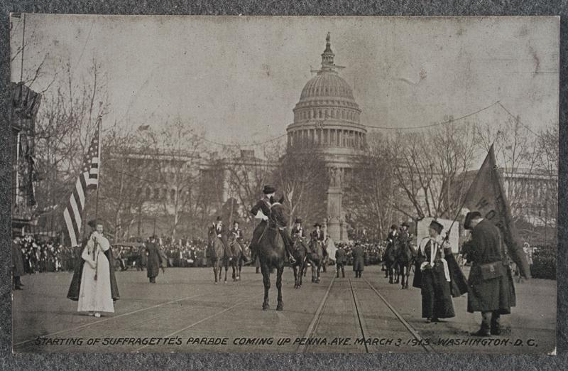 Grand Marshal Mrs. Richard Cook Burleson, mounted riders and flag bearers at beginning of suffrage parade. At right stands a photographer with his camera
