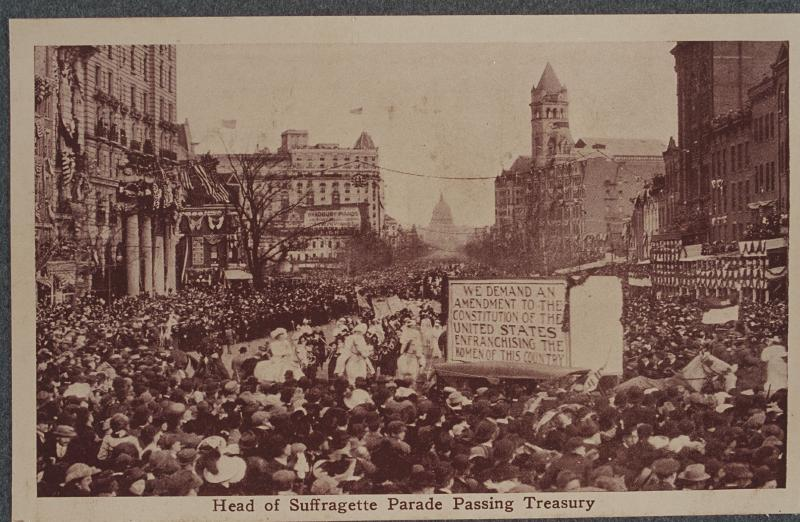 Black and white photograph of Suffrage parade passing by the Treasury Building as onlookers crowd the sidewalks