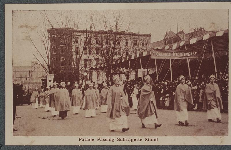Black and white photograph of uniformed nurses parading down a crowded street