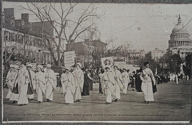 Black and white photograph of women marching in Suffrage parade with Capitol Building in the background