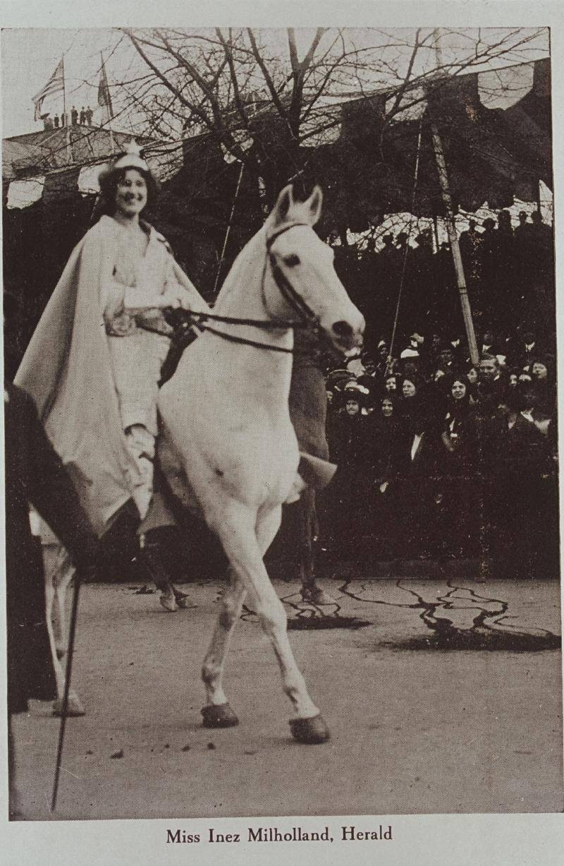 Photographic postcard of a woman riding a white horse in a suffrage parade